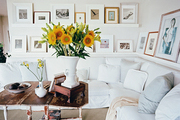 A gallery wall of art hung above a white sectional couch