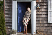 Michelle Smith striking a welcoming pose in the doorway of her Shingle Style Hamptons home