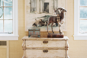 A rustic cabinet decorated with art and accessories