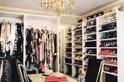 A walk-in closet with built-in shelves and a brass-and-Lucite chandelier