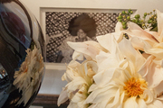 A sunny arrangement of dahlias in front of a framed picture