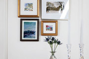 A vignette of framed photos in a whitewashed dining area