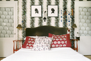 Silhouettes hung on floral wallpaper above a green velvet headboard