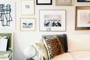 A gallery wall of art hung above a white couch and a green side chair
