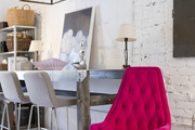 A tufted magenta chair and an iron pendant lantern at Buckingham Interiors + Design