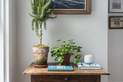 A wicker storage basket below an accent table topped with books and potted plants