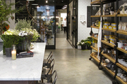 Open shelves of gourmet goods in a room with a marble-topped table and industrial bar stools