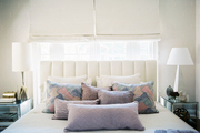 A white bedroom palette accented with purple throw pillows