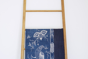 An indigo textile displayed on a wooden ladder