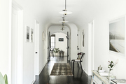 A hallway with dark wood floors and white walls.