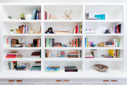 A white bookshelf filled with books and decor items.
