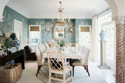 A wallpapered dining room filled with upholstered buffalo-check chairs and fretwork host chairs