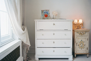 A white dresser beside a painted side table
