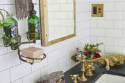 Toiletries sit on a bathroom vanity with gold hardware set against white subway tile.
