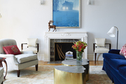 Large framed painting above fireplace in colorful living room.