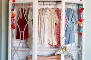 A shabby chic armoire holds children's clothes and blankets