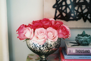 A silver vase of pink roses