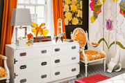 A pair of upholstered armchairs flanks a white bureau amid colorful curtains and accessories