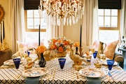 A dining table set for Thanksgiving below a crystal chandelier