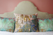 Multi-colored throw pillows in front of a padded headboard.