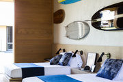 Colorful surfboards hang above twin modern bed-sets.