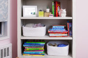 An RH Baby & Child Bellina Bookcase holding soft baskets of clothing, books, and decorative objects in a nursery