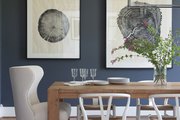 Large scale art and natural wooden table in contemporary dining room.