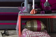 A display of tabletop items, textiles, and other accessories in a pink and gray palette