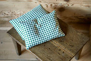 Green gingham pillow on wooden stool