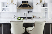 A dramatic black-and-white kitchen with lucite-and-gold light fixtures and glamorous accents