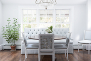 A breakfast nook with a tufted banquette, crystal chandelier, and round, wood pedestal table