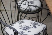 Wrought iron chairs with upholstered cushions at an outdoor seating area