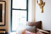 A built-in window seat with patterned pillows and a gold wall sconce