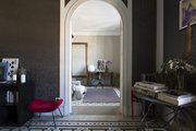 An arched doorway connecting two tile-floored spaces