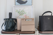 Handbags sit atop storage containers.