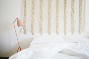 Tapestry hanging above white bedding.