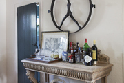 A carved-wood sideboard serving as bar and storage shelving in a Sag Harbor house