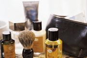 A leather travel case and a men's shaving brush on a snakeskin-print tray
