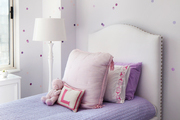 Pink and white girl's room with throw pillows and tall white headboard.