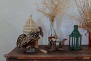 Figurines, lanterns, and vases of dried branches atop a wooden surface