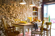 A stone-walled kitchen with light fixtures made from vintage porcelain dishes