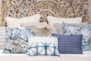 A shabby chic bed with blue and beige pillows.