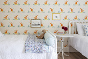 A children's room covered in a colorful sailboat wallpaper