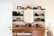 A gold mirror on a white bookcase filled with a shoe collection
