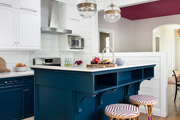 A contemporary kitchen with a blue island.