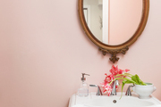 A pink bathroom with a gilded mirror.