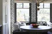 Patterned wallpaper and pillows contrasting with dark flooring and  banquettes in a breakfast nook