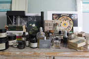 Perfume, books, and random objects in a decorative vignette