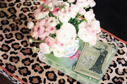 A tray with a book and flowers atop a leopard-print ottoman