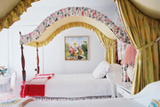 A pair of arched floral canopy beds dressed with white linens